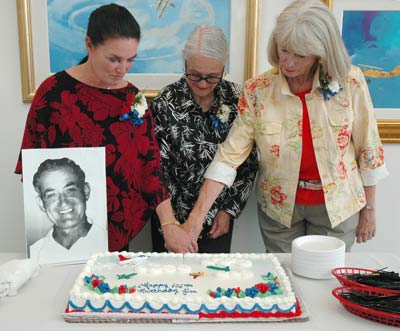 The daughters of Jim Walker cut the birthday cake